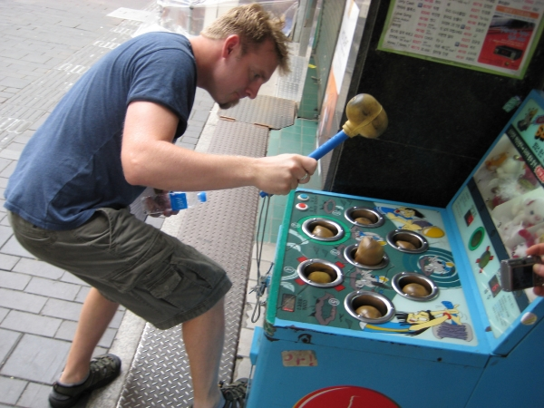 Man hitting whack-a-mole machine with a mallet